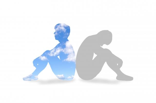 背中を合わせて体育座りをしている2人の画像