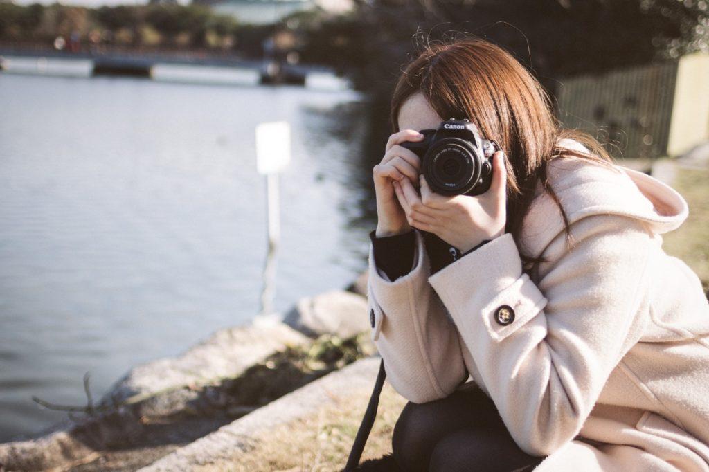 一眼レフカメラをこちらに向けている女性の画像
