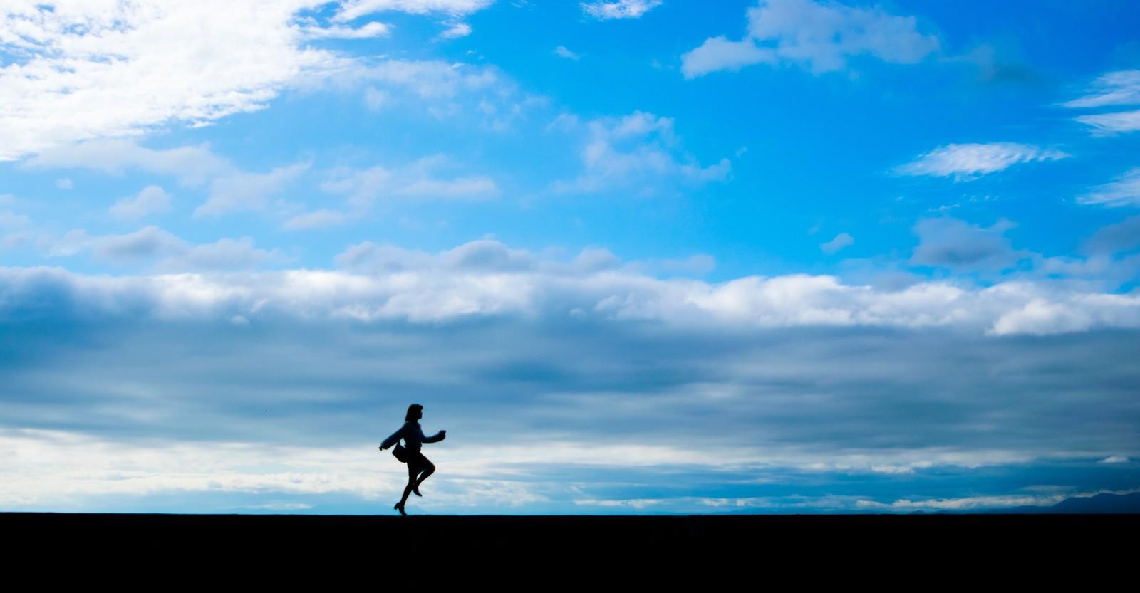 青空の中で、君の特別になりたいと土手を走っている人の画像