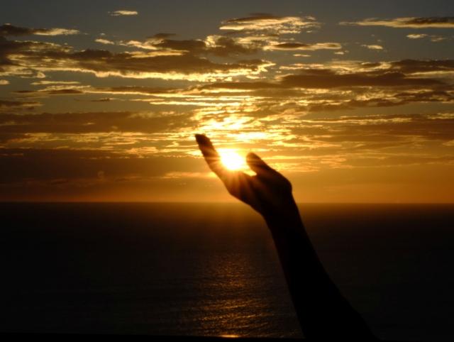 手のひらに遠近法で夕日を乗せている画像