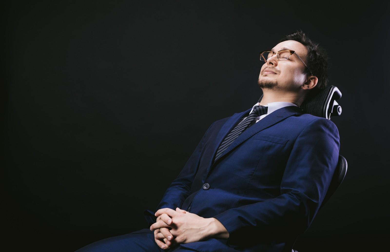 人生の休憩に入るかのようにソファで眠りにつくスーツ姿の男性の画像