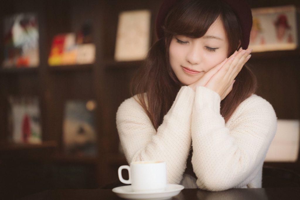 カフェでコーヒーを飲みながらスヤスヤ眠るようなポーズを取っている女性の画像