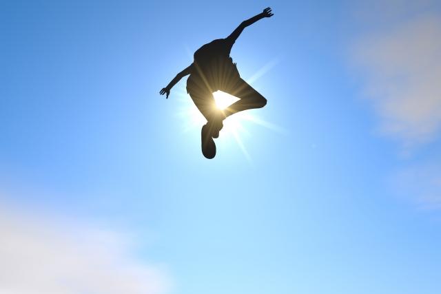 人生勝ち組だと叫びながら空高くジャンプしている男性の画像