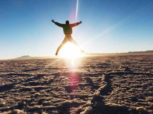 人生なんとかなると砂浜をジャンプしている男性のシルエットの画像