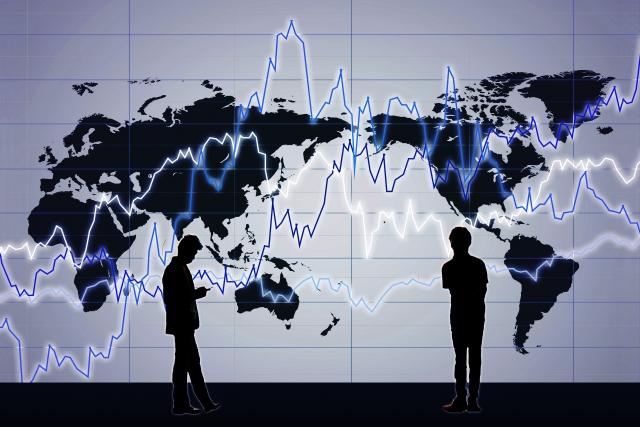 世界地図と2人の男性のシルエットの画像