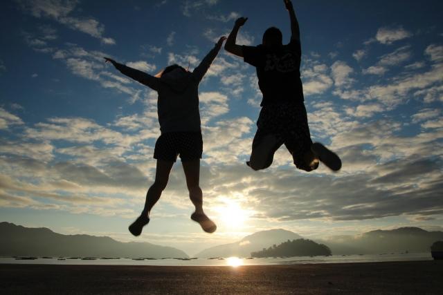 2人の男女がジャンプしているシルエットの画像