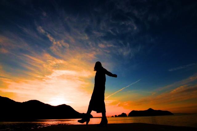 夕焼けの中散歩している女性のシルエットの画像