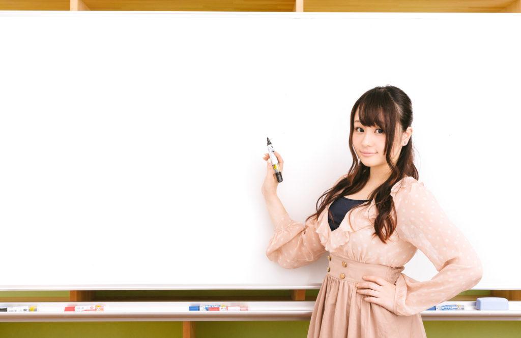 ホワイトボードの前で指導している女性の画像