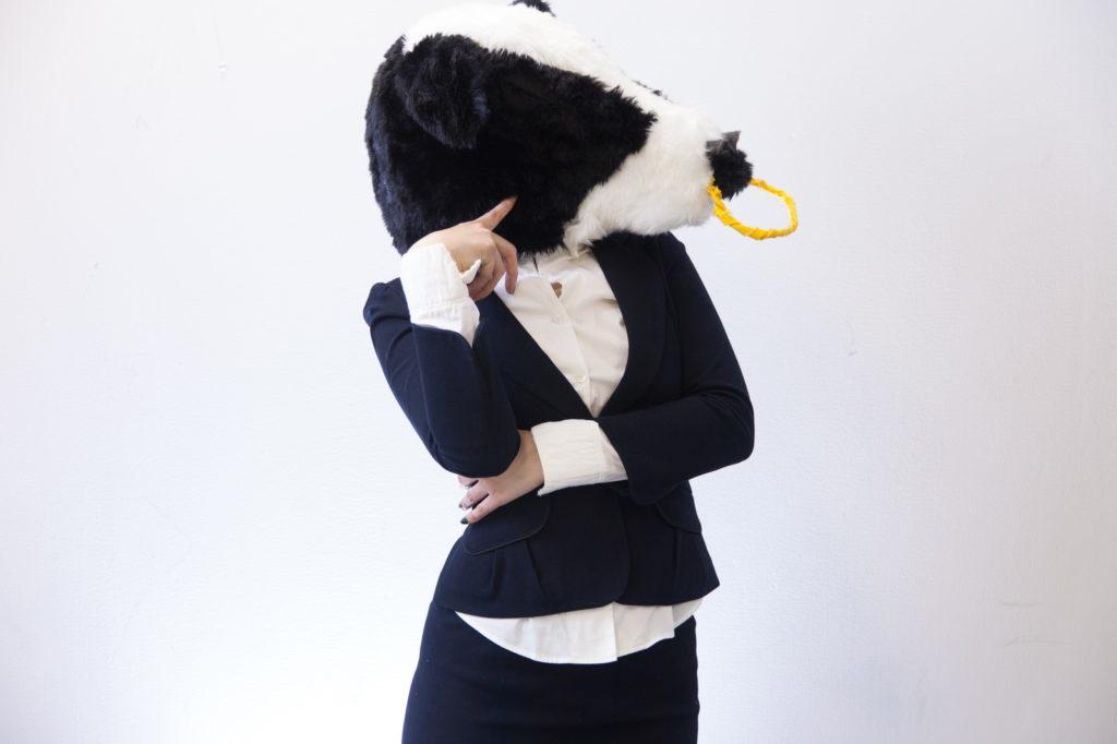 牛の被り物をしているスーツ姿の女性の画像