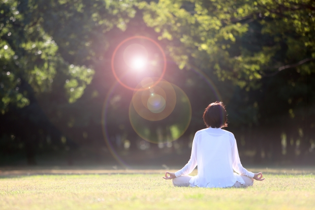 草原で瞑想をして心の浄化をしている女性の後ろ姿の画像