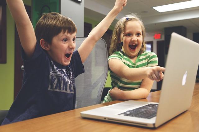 パソコンの前で手を上げて喜ぶ子供2人の画像