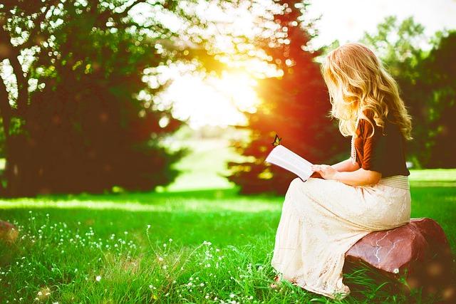 芝生で読書している女性の画像