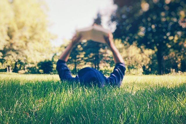 芝生に寝っ転がりながら本を読んでいる男性の画像