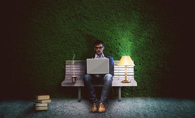 暗いベンチでパソコンを開いてブログを書いている男性の画像