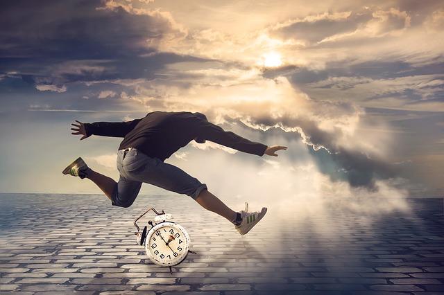 人生の時間を知らせる目覚まし時計とジャンプしている男性の画像