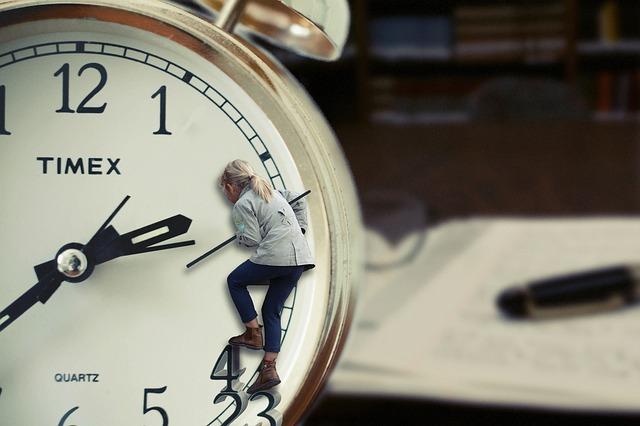 時間が足りないと目覚ましの秒針を止めている女性の画像