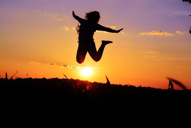 夕日の中で大きくジャンプしている女性の画像