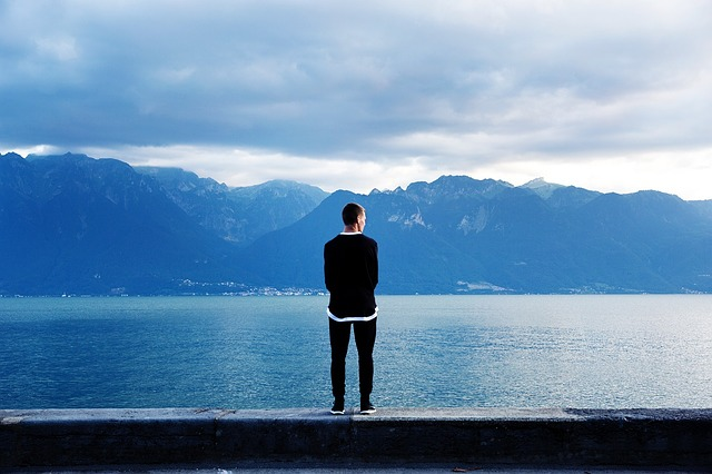 湖を眺めている男性の後ろ姿の画像