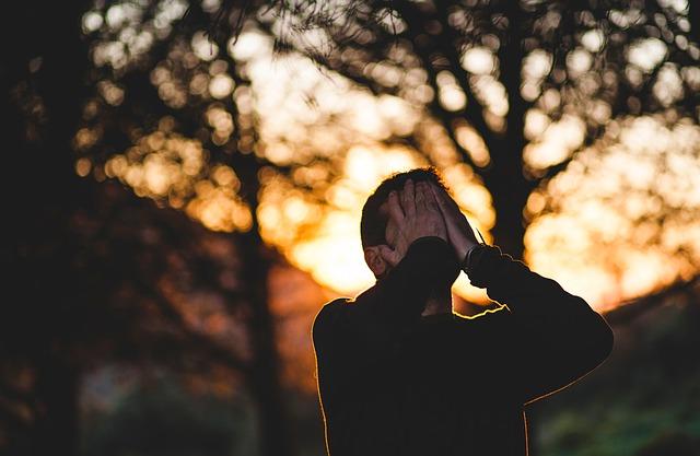 人生後悔することがあって両手で目を抑えて泣いている男性の画像