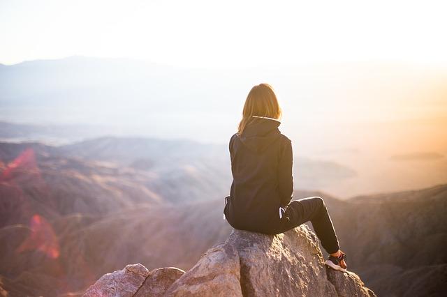 崖の頂上で座って夕日を見ている女性の画像