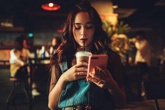 スマホをいじりながらドリンクを飲んでいる女性の画像