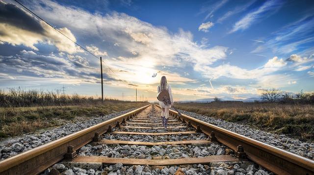 広大な道にある線路の真ん中を歩いている女性の画像