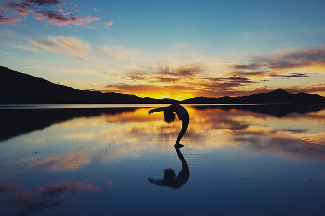 夕日の中の湖の真ん中で後ろに体を反り返っている女性の画像