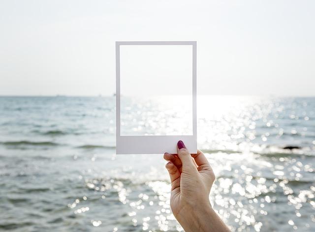 朝日に照らされた海にフレームを当てはめている女性の手の画像