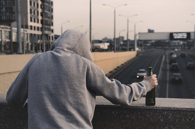 陸橋でスロットやめたいとつぶやきながらお酒を飲んでいる男性の後ろ姿の画像