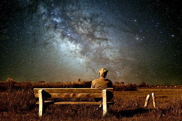 ベンチに座って綺麗な星空を見ている男性の画像