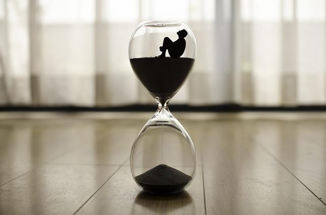 時間は有限と考えながら砂時計の中にいる男性のシルエットの画像