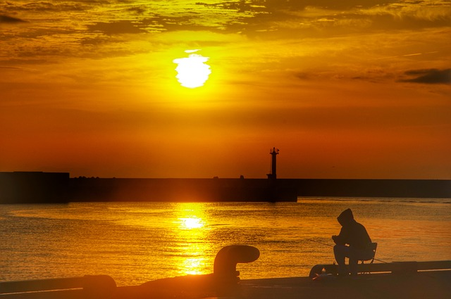夕焼けに染まった海で、ひきこもりでニートの男性が悩んでいる姿の画像