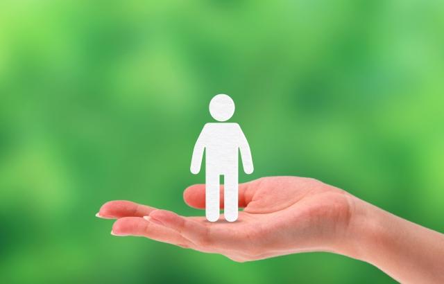 人の形をした紙を手のひらに乗せている画像