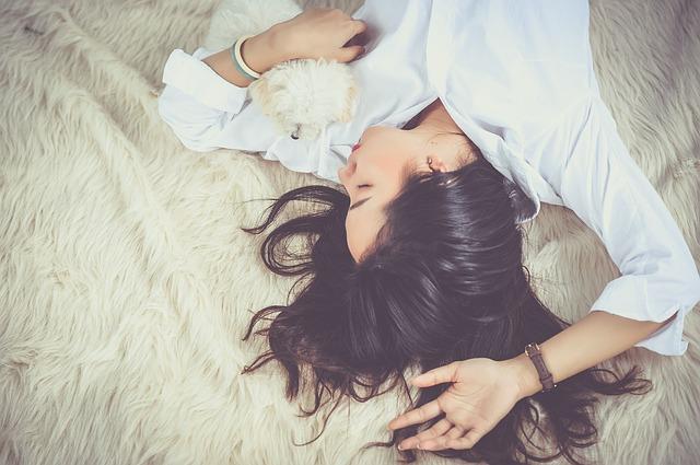 ベッドの上でペットと寝ている女性の画像