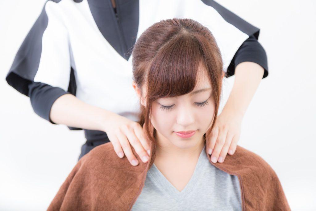 肩をマッサージしてもらっている女性の画像