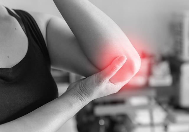 肘を痛めている女性の画像