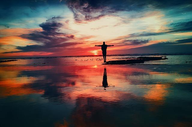 夕焼けに染まる海で手を広げる男性の後ろ姿の画像