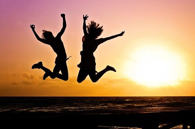 2人の女性が夕焼けの中ジャンプしている画像