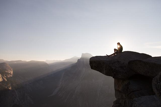 崖の上で座っている男性の画像