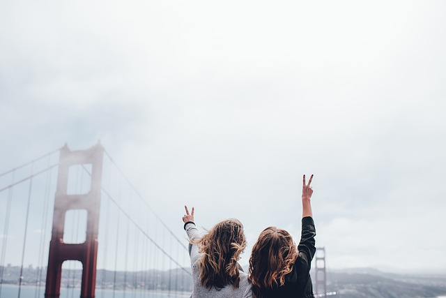 2人の明るい女性が空に向かってピースしている画像