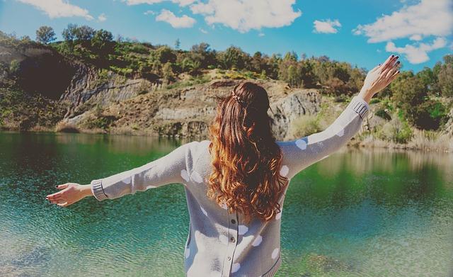 湖の前でバンザイしている女性の画像
