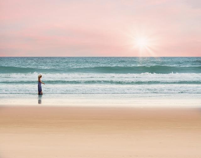 海の浜辺で歩いている女性の画像