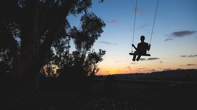 夕焼けの中ブランコに乗っている男性のシルエット画像