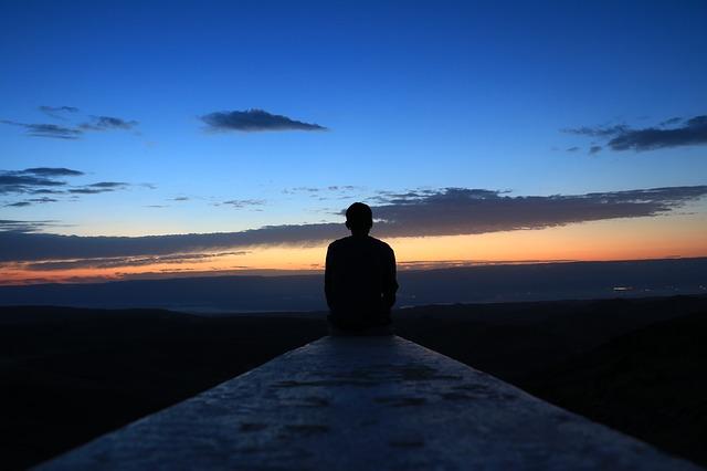 夕暮れの海で1人で座っている男性の後ろ姿の画像