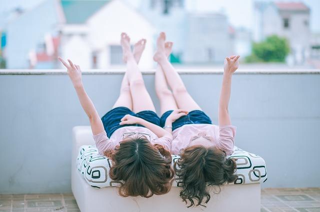 双子の女性がベッドで話している画像