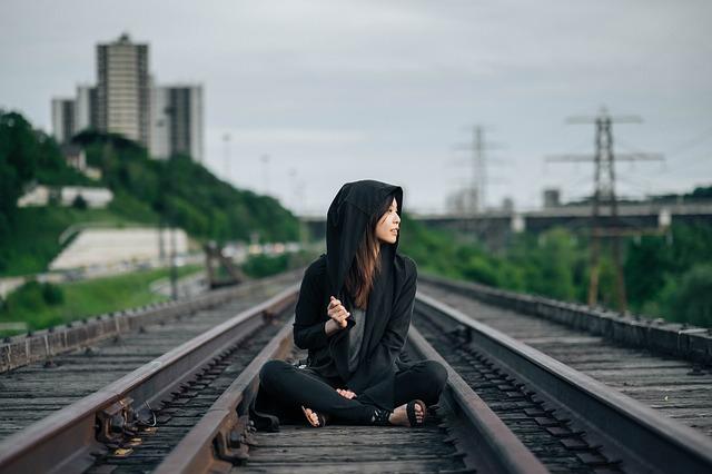線路に座っているフードを被った女性の画像