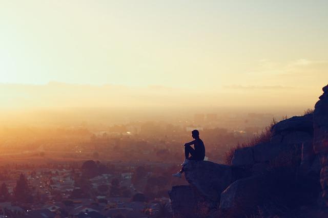 自分に正直に生きた男性が崖に座っている画像