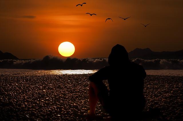 夕日を眺めている男性の後ろ姿の画像