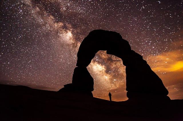 星空の下の岩に立っている人の画像
