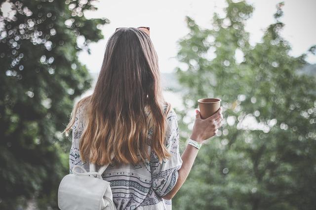 片手にコーヒーを持っている女性の画像